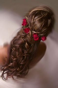 A half-up hairstyle interwoven with red roses is perfect for a classic fairy tale wedding.