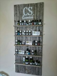 DIY pallet essential oils shelf. Pallet pieces ripped in half for shelves, pallet piece back, quarter inch plywood backing to hold the strips together. Metal rod bent and inserted in holes to create guard rail. Wood screws to hold shelves on (pre-drilled). 2 hour project.