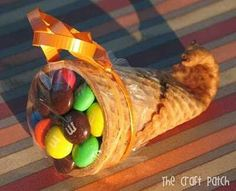 Mini cornucopia Dip tip of cone in warm water for 20 seconds and put in microwave for 20 seconds. Roll tip around a clean pencil for about 20 seconds and fill with m's, covet with plastic wrap and add ribbon.