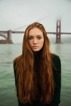 Fair-skinned befreckled blue-eyed copperhead w/ waistlength hair in forest knit turtleneck before San Francisco bay w/ Golden Gate Bridge in fog