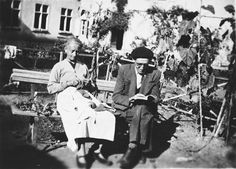 Mr. and Mrs. Nadal, Spanish refugees and staff of Chateau de la Hille, relax outside by knitting and reading.La Hille, [Ariege] France