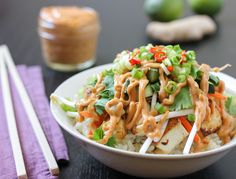 This burrito bowl is a simple Thai twist on a regular burrito. Fresh carrots, cucumbers, bean sprouts, cilantro, green onions and Thai chili peppers sit on top of ginger-infused jasmine rice and sweet and spicy tofu. It's all coated in a sweet, tangy and slightly spicy peanuty-Massaman Curry sauce.