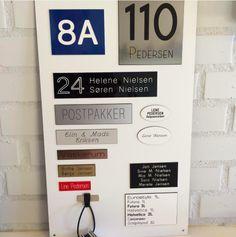 Udstillingstavle med eksempler på skilte med husnummer, postkasseskilte, dørskilte, navneskilte og meget mere.