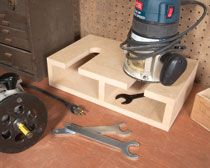 Stand for 2 Routers - Made with 3/4-in. MDF. It measures 4 in. tall by 9-1/2 in. deep by 16 in. wide. Each slot measures 2 in. wide by 6 in. deep. Drill a 2-in. hole at the back of each slot and cut out the rest of the slot on the bandsaw. Router wrenches and extra collets fit nicely under each router.