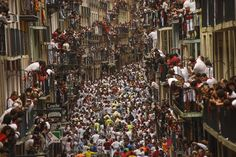 """People look on from balconies as """"Jose Escolar Gil"""" fighting bulls prepare to run down Estafeta Street, during the fifth running of the bulls, at the San Fermin Festival, in Pamplona, Spain, July 11, 2015. Revelers from around the world arrive to Pamplona every year to take part in some of the eight days of the running of the bulls."""