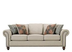 For a timeless living room with classic appeal, call on the Corliss sofa. This piece will make a grand statement with its generously scaled seating and oversized nailhead trim adorning the ever-stylish rolled arms. The oatmeal-colored fabric is so versatile, and it's complemented beautifully by bold prints on the accent pillows. Plus, its turned feet are finished in an attractive walnut tone that goes with everything.
