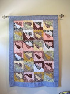 Tip to hang a quilt to display on the wall: There are many ways to hang a quilt for display. One is to sew a sleeve (fabric tube) on the back of the quilt near the top and slip a rod through it.