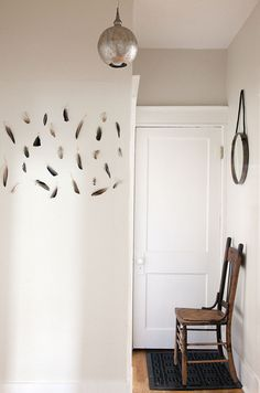 A boho-chic feather wall installation adorns the entry way of a traditional home in Nashville.