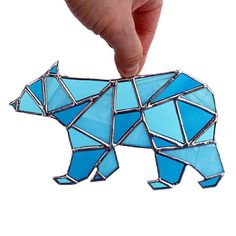 Handmade geometric polar bear stained glass sun-catcher. Beautiful blue glass in geometric shapes is used to create the stained glass bear sun catcher. Sun catcher is 6.5 x 4. This polar bear is made of different shades of blue glass with a silver finish. Comes with a suction cup