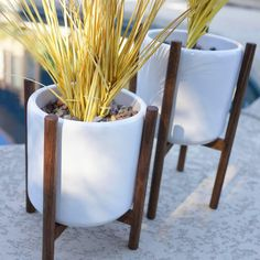Staggered Pair of Modern Mid Century Eames Era Style Ceramic & Walnut Quad Base Planters Excellent condition, staggered pair of genuine walnut, quad-base planter stands and ceramic planters. The tall one measures about 12 inches tall, 8 inches across with the legs. The shorter one measures about 9 inches tall, 8 inches across with the legs. The classic-style, cylinder shaped pots are 6.5 inches across by 6 inches tall. Genuine walnut, hardwood bases have been detailed and finished in an e...