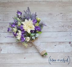 This wildflower bouquet is full of lavender, purple wildflowers, purple thistles, greenery and ivory/cream dahlias.