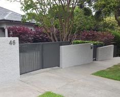 A unique front fence built by Black Barrow in Melbourne. Australia. The fence was constructed using reinforced concrete blocks, rough-cast render and powder-coated metalwork. The fence was designed to take advantage of the sloping site and to minimise damage to the established garden and paving during construction.