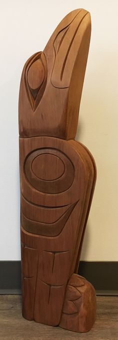 """Single-figure Totem carved by Coast Salish artist Doug Horne. This small red cedar totem depicts the mischievous creator, Raven. The piece measures 31"""" X 8""""."""