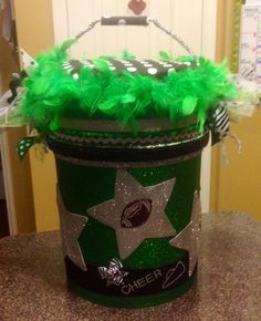 Cheer Bucket *Adding materials used to make* 1-5 gal bucket Foam & material to make bucket seat 4-green, foam glitter sheets from Hobby Lobby 3-silver, foam sheets (stenciled & cut out stars) 1-green boa from the $Tree Lots of ribbon trim!! Glitter stickers from Hobby Lobby Hot glued everything to bucket :)