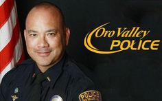 Photo of Lieutenant Chris Olson with flag background and Oro Valley Police logo