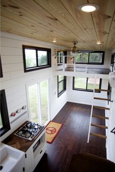 Handscraped chocolate birch flooring and dark window trim contrast nicely with the white shiplap walls and natural wood ceiling.