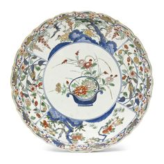 THE PROPERTY OF A PRIVATE TRUSTAn Imari DishEdo period (late 17th - early 18th century)The moulded foliate-rimmed dish painted in various coloured enamels and gilt on underglaze blue with a central roundel enclosing sprays of chrysanthemums and peonies in a basket, surrounded by four panels of various flowers including camellia, wisteria, peonies and cherry blossoms, a band with plum, pine and bamboo to the rim, the reverse with clematis flowers and scrolling foliage, a band of stylised…