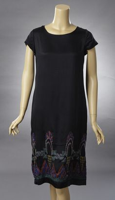 1920s Black silk sheath with a widely scooped neckline. The dress is decorated with a geometric hand painted design in red, green, blue and Chartreuse. The hand painted design is accented with crystal beads in silver blue green and clear. Front