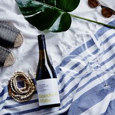 Square photograph of some shell beads, leather slide sandals, white wine and a large leaf lying on a striped beach towel.