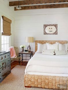 Yes, you can love both modern and rustic bedroom ideas and bring them together successfully where you sleep. In this room, playful, contemporary artwork and a sleek, sophisticated chrome lamp balance the look of a texture-rich woven rope bed paired with a primitive chest of drawers, still wearing its original chipped paint. Rustic beams, shiplap walls, and a woven window shade echo the furnishings and help unify seemingly disparate pieces. /