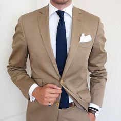 A great look! Mens tan suit with navy knit necktie