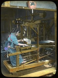 A woman weaving silk in an old fashioned loom (home made)  Enami Studio Lantern Slide No : 643.  About 1920's, Japan