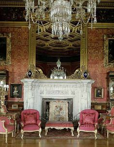 18TH  Alnwick Castle,Northumberland:chimney-piece with mirror,arm-chairs and chandelier.  Alnwick Castle, Alnwick, Great Britain