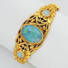 Antique Opal and 24K Gold Bangle Bracelet, circa 1900   The oval hinged hoop featuring an oval opal measuring 20.5 mm by 15.0 mm, between a pair of smaller opals, amid a pierced floral ground, inner circumference 6 1/4 ins