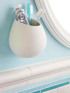 The vanity or sink top is generally the only counter surface in a small bathroom. Maximize that space by making smart storage choices. Corral dental care items -- ones that often gobble up counter space -- in wall-hung containers that are dishwasher-safe, such as this kitchen utensils holder. Attach it to a wall using an anchor screw.