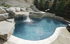 How do you accommodate family fun with a severely sloping backyard? This Toronto family created multiple outdoor living spaces at descending levels. First, an outdoor dining terrace, then a recreation terrace with small pool and patio, finally a section of lawn for a children's play area. The pool features a swim jet for exercise, a rock feature with waterfall grotto where the kids huddle behind the flow, and an elevated spa that spills into the pool. The Indiana limestone coping and patio…