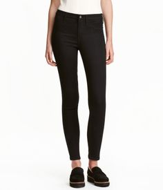 Black denim. Ankle-length jeans in washed stretch denim with a regular waist. Mock front pockets, regular back pockets, and skinny legs.