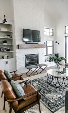 Gorgeous modern farmhouse living room designed by Sita Montgomery Interiors - white brick fireplace simple wood mantel leather slingback chairs layered rugs circular coffee table and sconce lighting above open shelving - April 27 2019 at Design Living Room, Family Room Design, My Living Room, Living Spaces, Cozy Living, Small Living, Living Room Brick Wall, Brick Wallpaper In Living Room, Living Room Fire Place Ideas