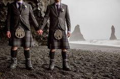 Grooms in kilts hold hands as they stand on Icelandic coast.