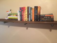 Floating bookshelf in bedroom made of reclaimed wood that we planed and stained. Supported by metal pegs made from flanges, nipples and caps.