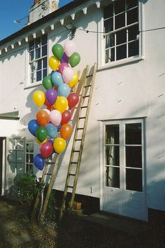 Here's an easy way to add some color to any party: tie balloons up the length of a ladder and lean against a wall.   via Plenty of Colour