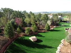 Since this backyard has it's own, personal putting green, you will never have to leave home again! This space is bordered by #local #Colorado trees, shrubs, and wildflowers!  #Home #Patio #Deck #Waterfall #Landscape #Custom #Colorado #Outdoors #ColoradoCustomDecks #MosaicOutdoorLiving Find us at http://coloradodecks.com/