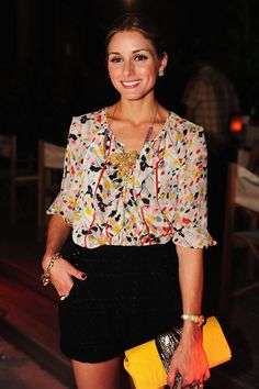 Flower print blouse paired with loose fit black shorts and a yellow clutch. Perfect look for dinner out.