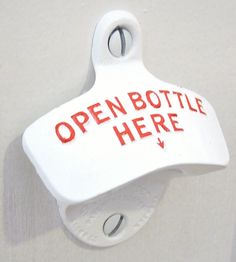 A classic white wall-mounted bottle opener