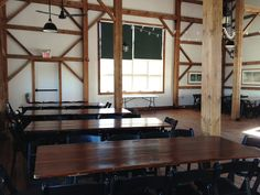 The Byron Colby Barn is a restored historic barn, built with materials dating back to 1885. The main floor is furnished with dark cherry stained wooden tables and comfortable black folding chairs, ready for your decorative touch.