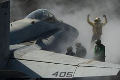 ABH3 Eric Welsh directs an F/A-18C Hornet assigned to Strike Fighter Squadron (VFA) 25 onto the bow catapults for launch on the flight deck aboard aircraft carrier USS Carl Vinson (CVN 70).