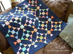 """Rebecca made this beautiful quilt called Aura. She used a navy solid from Primitive Muslins by Moda for the background and i love how it makes the colors sparkle. The pattern is available in Rebecca's new book called Seamingly Scrappy."""