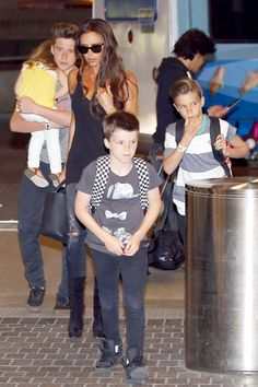 Victoria Beckham and her kids make their way through the LAX