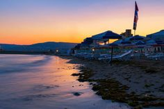 Beach with umbrellas on black sea coast at dusk after sunset in Balchik city stock photo