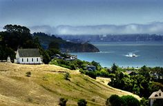 On Monday July 27 2009, Old St. Hilary's Church sits on a hillside in Tiburon Calif., contrasting with the skyline of San Francisco across the bay. Morning fog hangs in the air. (IJ photo/Frankie Frost)
