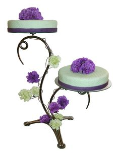 Two cakes placed on multilevel stand. Real flowers to match colors of wedding celebration