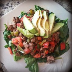 Mexicali from #ItStartsWithFood over a bed of baby spinach stopped with sliced avocado. 1lb grass fed beef seasoned with cumin, himalayian sea salt, pepper.. diced tomatoes, onion and red-green peppers