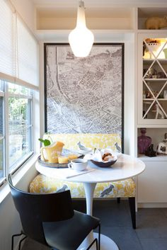 Here, a large map framed in raw steel with brass screws behind a yellow and white toile bench adds interest to this midcentury galley kitchen and ups the gravitas of the cozy breakfast nook.
