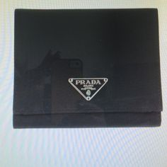 Prada wallet Authentic Prada wallet made from Tessuto black nylon with saffiano leather lining. The wallet is Tri fold and opens to 7 credit card slots a flap and snap closure, zippered coin pocket and a slot for dollar bills. Prada Bags Wallets