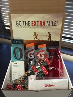Go the Extra Mile Box | Encourage people to get active with this gift box that includes a FitBit, sweatband, water bottle, Gatorade pouches, and kind bars.