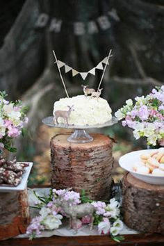 rustic nature inspired woodland baby shower with tree backdrop dessert table with cake on wood trunk stand